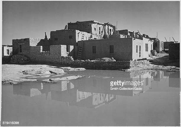 A black and white exterior photograph of an adobe house the multistory home consists of several sections that are in various stages of completion a...