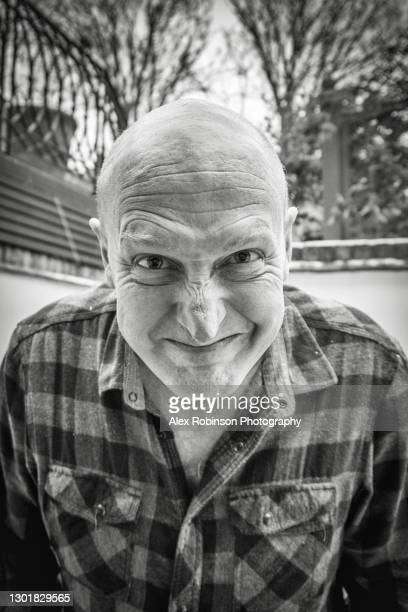 black and white head shot of a bald man in his fifties pulling a face - ugly bald man stock pictures, royalty-free photos & images