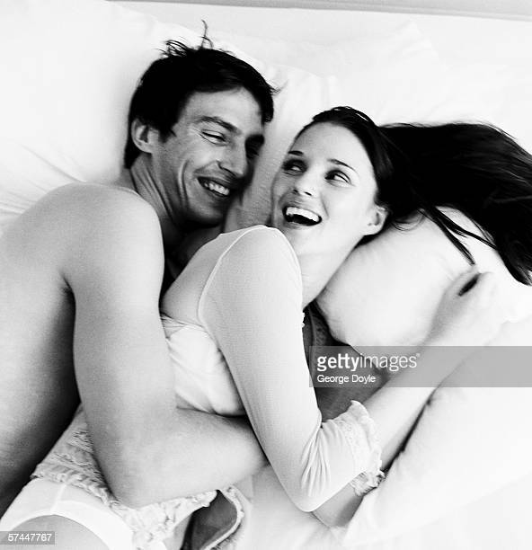 black and white high angle view of a couple hugging in bed and smiling at each other