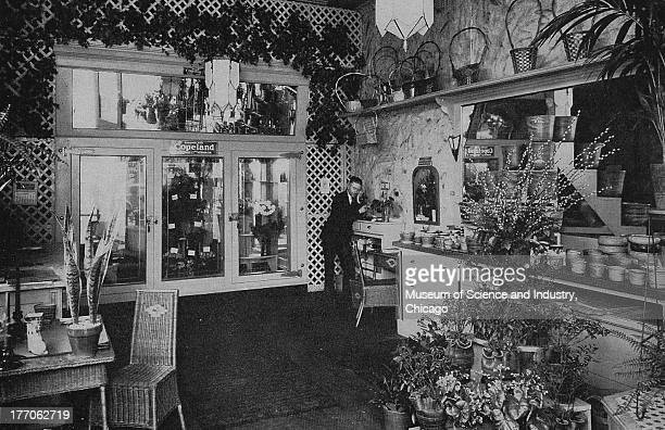 A black and white image of a Florist Shop showing an image of a small florist shop with flowers and baskets displayed around the store and a man on...