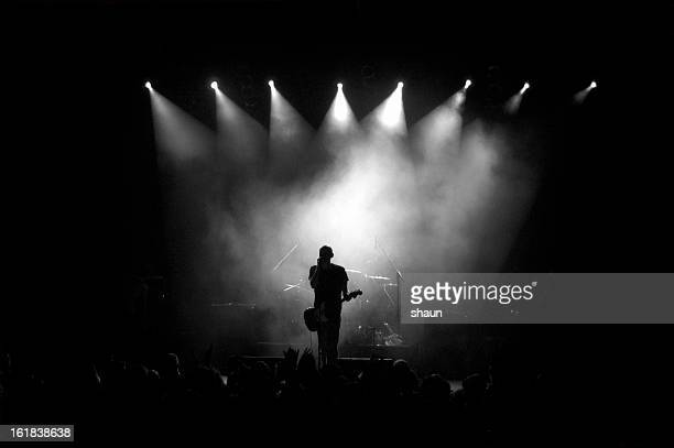 black and white image of a guitarist on stage in fog  - musician stock pictures, royalty-free photos & images