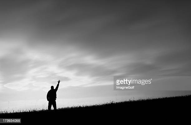 Black and White Image of a Man on a Hill Reaching To Heaven