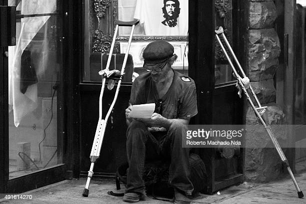 DOWNTOWN TORONTO ONTARIO CANADA Black and white image of an old man in torn clothes writing on paper with underarm crutches by his side Disabled man...