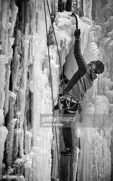 CONTENT] Black and white image of ice climber with ice axe climbing ropes carabiners helmet and crampons