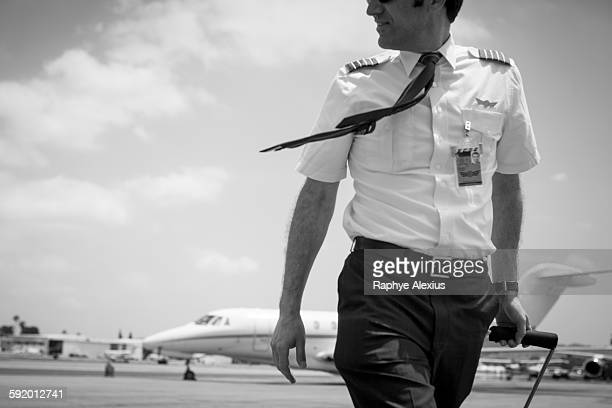 Black and white image of male private jet pilot arriving at airport