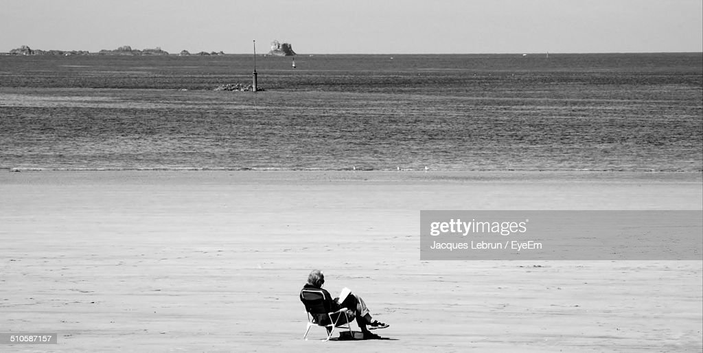 Black and white image of old man reading book at beach stock photo
