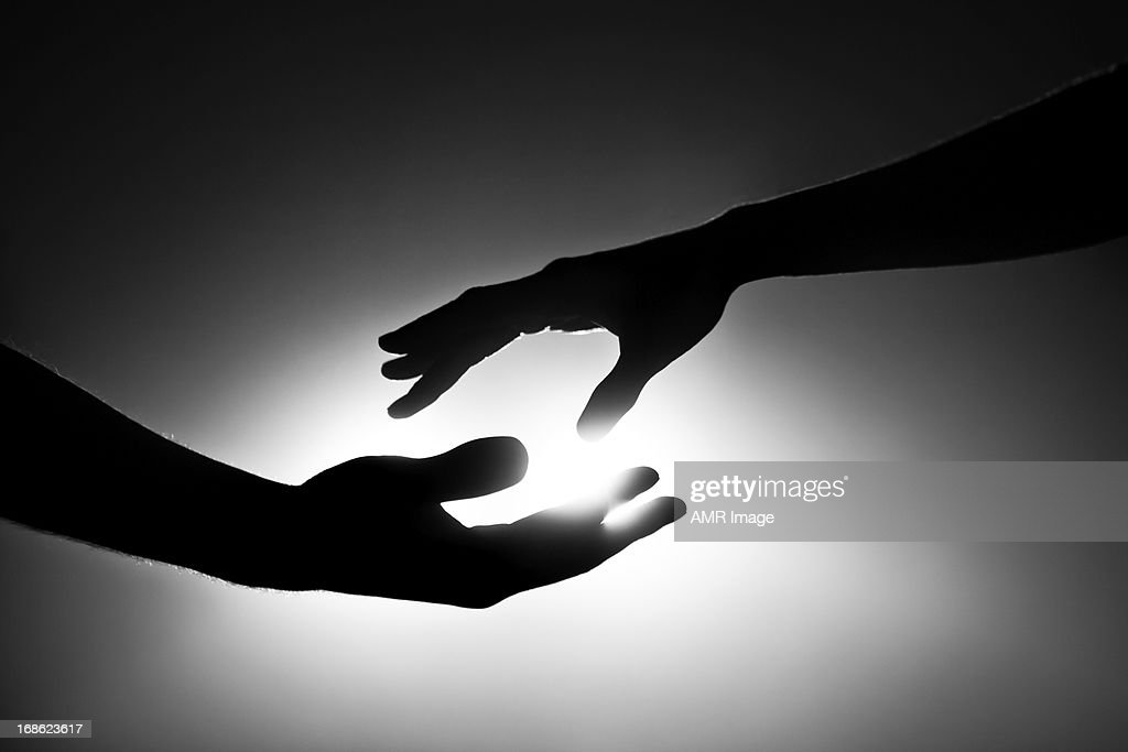 Black and white image of two hands reaching out : Stock Photo