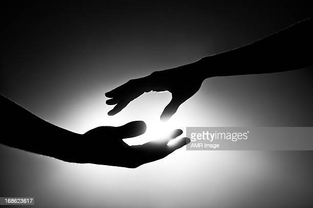 black and white image of two hands reaching out - reaching stock pictures, royalty-free photos & images