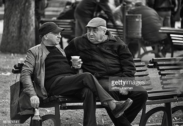 Black and white image of two older gentleman sitting and talking on a park bench. They are both wearing caps and one is holding a glass of beer in...