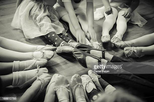 Black and white image of young girls feet wearing ballet shoes. Sitting in a circle with the teachers feet as well.