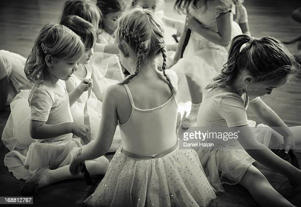 Black and white image of young girls sitting on the floor during a ballet class.