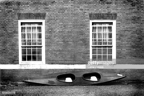 Black and white kayak leaned against a brick wall
