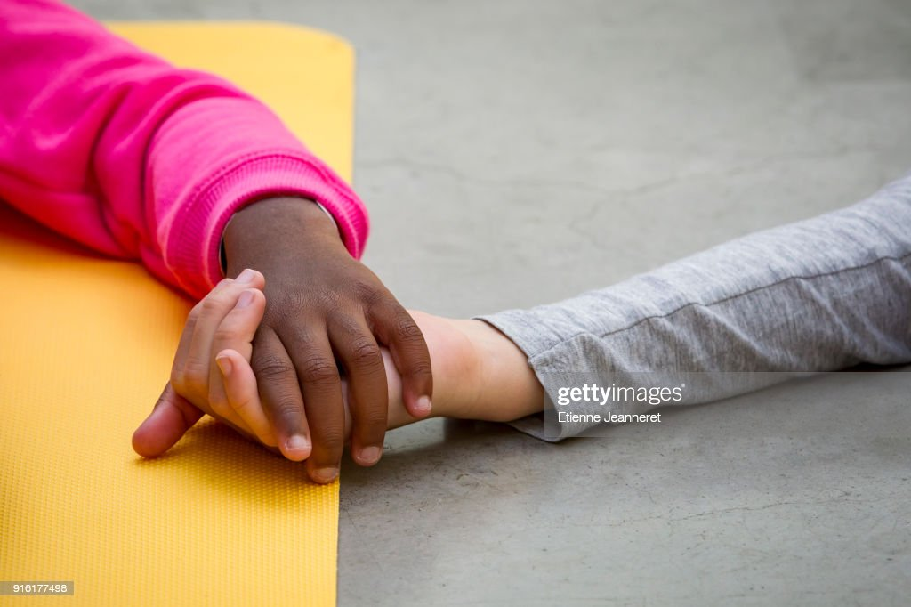 Black and white kids holding each other hands, Paris, France : Stock Photo