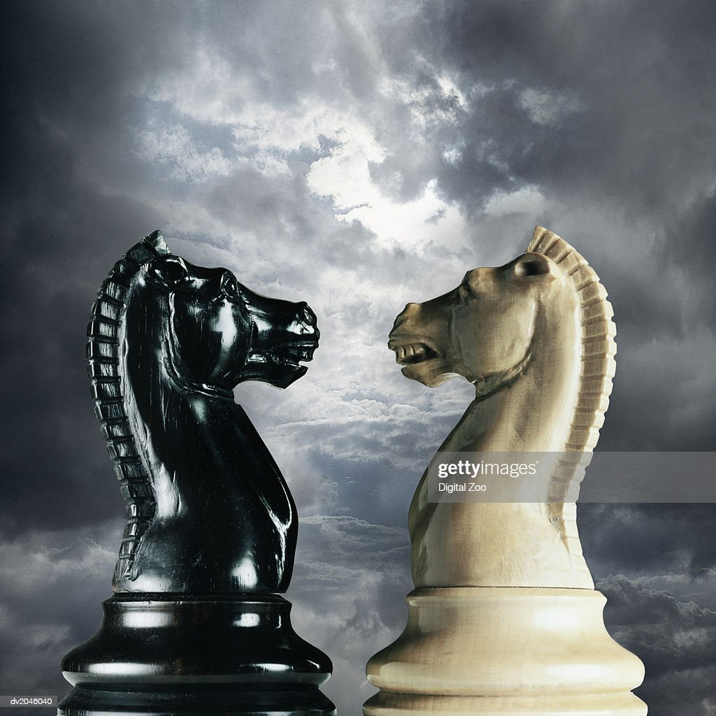 Black and White Knight Chess Pieces Snarling at Each Other, Stormy Sky in the Background : Stock Photo
