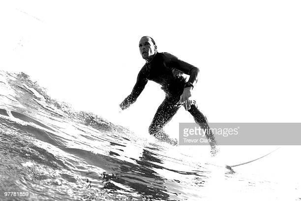 Black and white low angle perspective of a surfer riding a wave,
