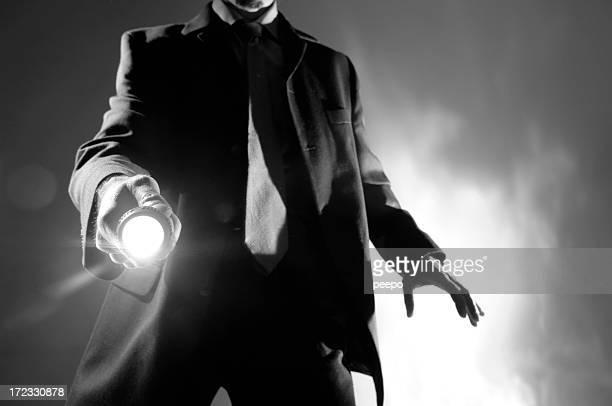 Blanco y negro hombre en traje con linterna