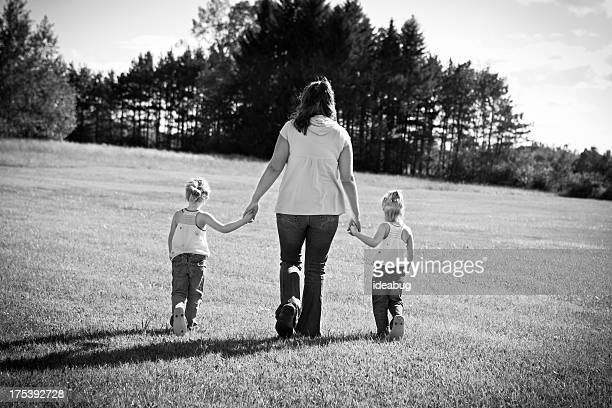 Black and White of Mother Walking With Twin Girls Outdoors