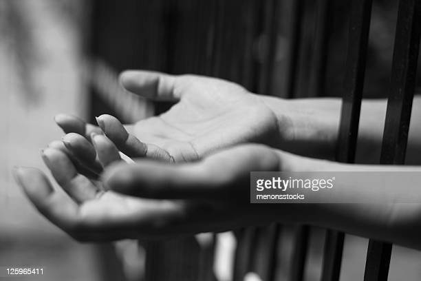Black and white pair of hands poking through jail cells