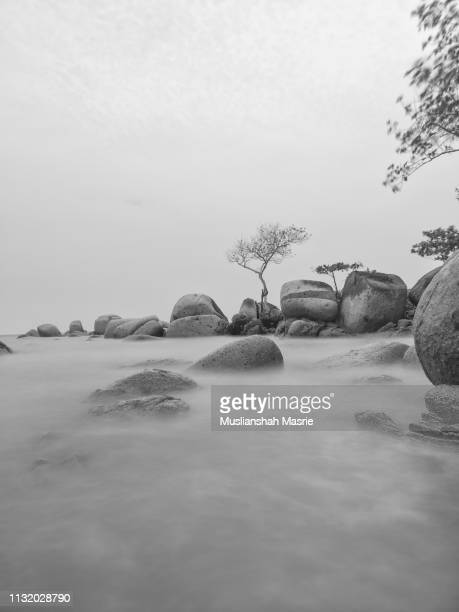 black and white panoramic long exposure shot of rocky beach during cloudy and monsoon day. - west kalimantan stock pictures, royalty-free photos & images