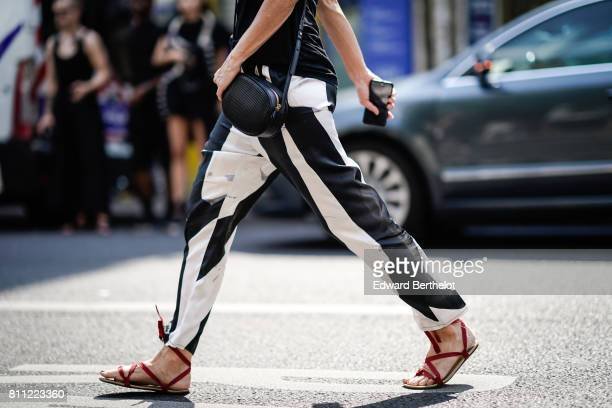 Black and white pants a black leather bag and red flat gladiator shoes are seen outside the Y/Project show during Paris Fashion Week Menswear...