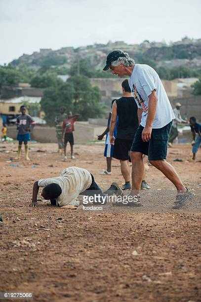 Black and white people playing soccer in a african village