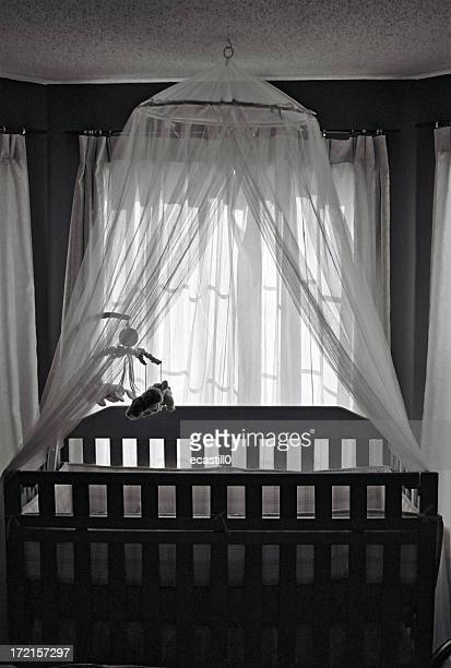 Black and white photo of a crib in a baby bedroom