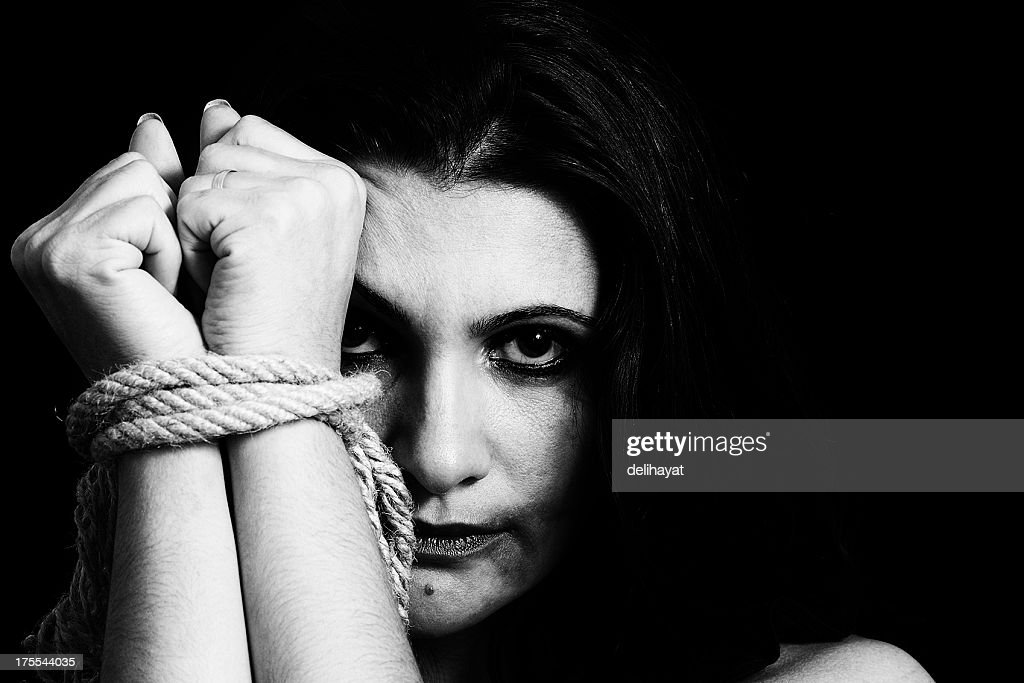Black and white photo of a woman upset with her hands tied : Stock Photo