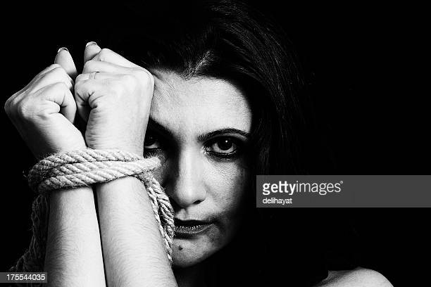 black and white photo of a woman upset with her hands tied - human trafficking stock photos and pictures