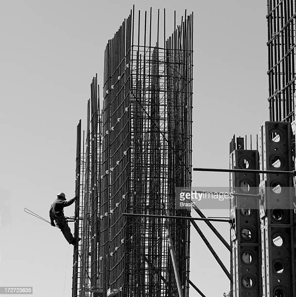 Black and white photo of construction worker on supports