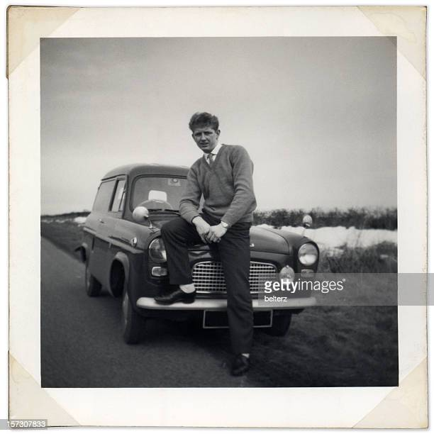 Black and white photo of man sitting on vintage car bonnet