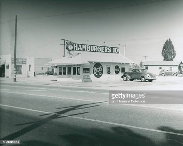 Black and white photograph featuring exterior of restaurant with clock parked car and sign advertising hamburgers for 10 cents