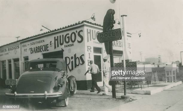 Black and white photograph featuring outside of restaurant with car parked in front and large sign with parrot
