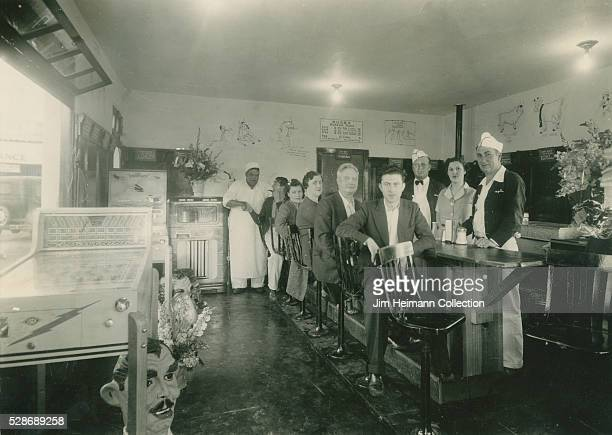 Black and white photograph featuring staff and patrons in restaurant with pinball machine