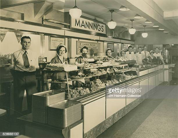 Black and white photograph featuring staff posing in line behind glass counter in Mannings restaurant