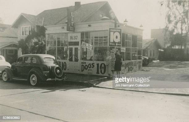 Black and white photograph featuring two women standing in front of Hugo's Hot Dogs by parked cars