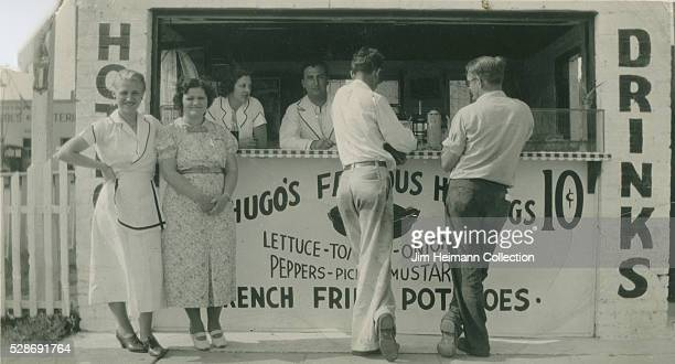 Black and white photograph men and women dining at stand and staff behind counter