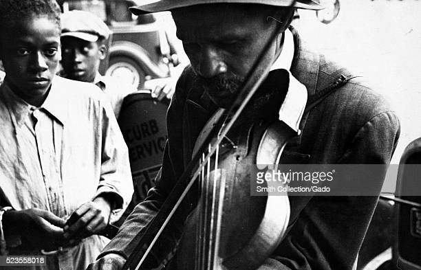 Black and white photograph of a blind AfricanAmerican man street musician playing the violin two AfricanAmerican boys in the background by Walker...