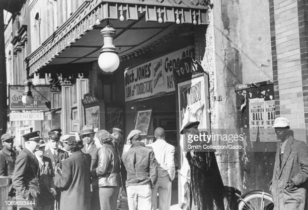 Black and white photograph of a group of men and women standing outside a cinema waiting to be allowed in with signs advertising Buck Jones Law of...