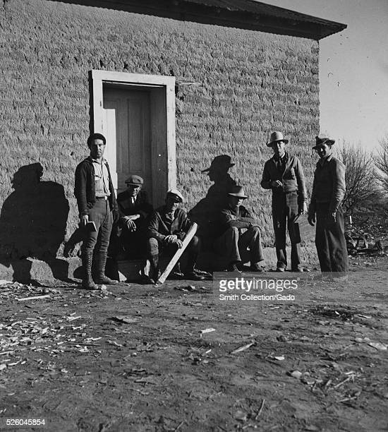 Black and white photograph of a group of men standing in front of a building titled Surveying gang WPA Workers Bosque Farms Project by Dorothea Lange...