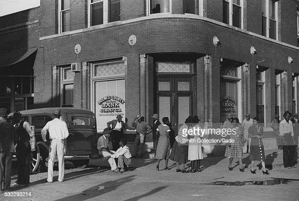 Black and white photograph of a large group of AfricanAmerican people standing and walking in front of a bank on a Saturday afternoon Lexington...