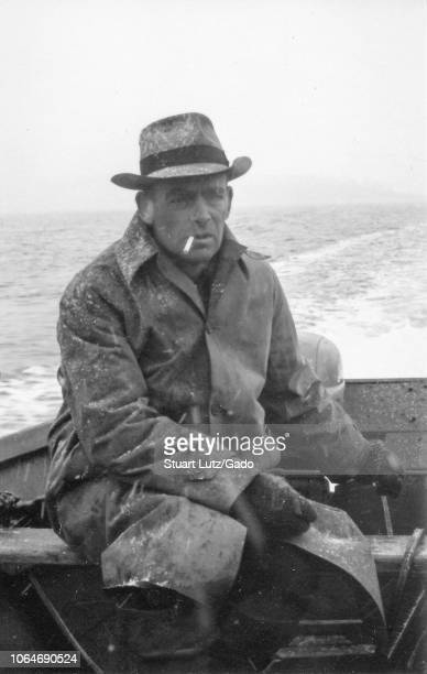 Black and white photograph of a middleaged man with a cigarette between his lips wearing a snowdusted coat gloves and hat sitting in the stern of an...