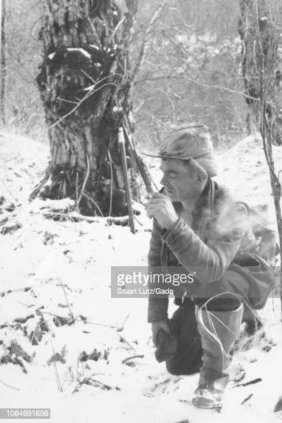Black and white photograph of a middleaged man with his eyes closed wearing a leather jacket boots and a hunting cap kneeling on one knee in the snow...