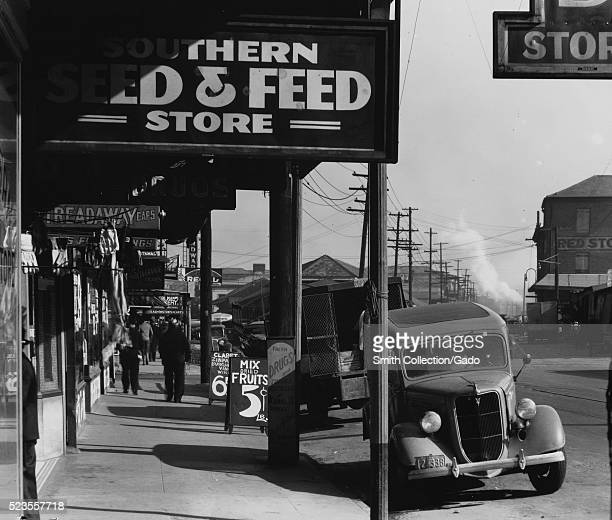 Black and white photograph of a sidewalk lined with stores cars parked on the street by Walker Evans American photographer best known for his work...