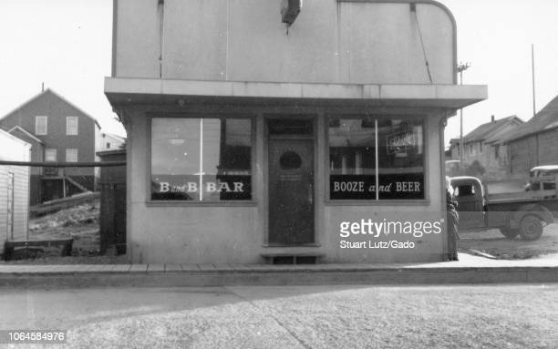 Black and white photograph of a small building with an Art Decoera facade and text in the windows reading 'B and B Bar' and 'Booze and Beer ' with...
