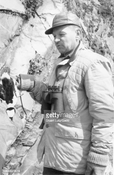 Black and white photograph of a squinting middleaged man seen in threequarter length profile view wearing a hunting jacket and a cap with binoculars...