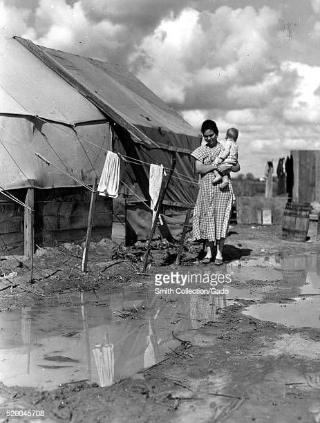 """Black and white photograph of a woman holding an infant, walking in a wet, muddy camp, """"titled """"Migrants' Camp"""", by Dorothea Lange, American..."""