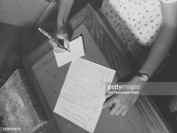 Black and white photograph of a worker taking notes about a document at the Frederick Douglass Memorial Home, the document is a letter from the...