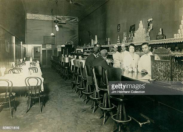 Black and white photograph of bar interior with tow patrons sitting on stools and four staff members behind bar
