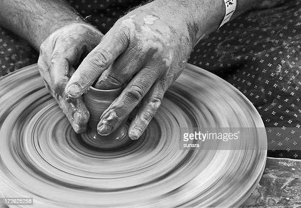 A black and white photograph of clay on a potters wheel