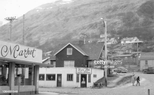 Black and white photograph of commercial and domestic buildings in a small town in Alaska with a concrete deco storefront at left with the sign...